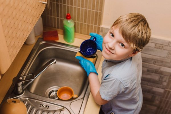 A boy helps his mom perform a housework. A boy in protective blue rubber gloves washes cups in the kitchen.