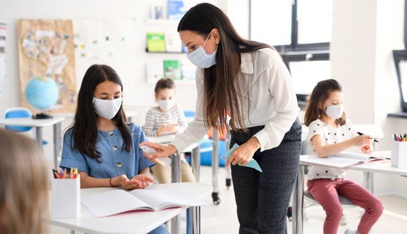 Teacher and children with face mask back at school after lockdown, disinfecting hands.